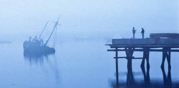 Boats in a harbor on a foggy morning in Cape Cod.