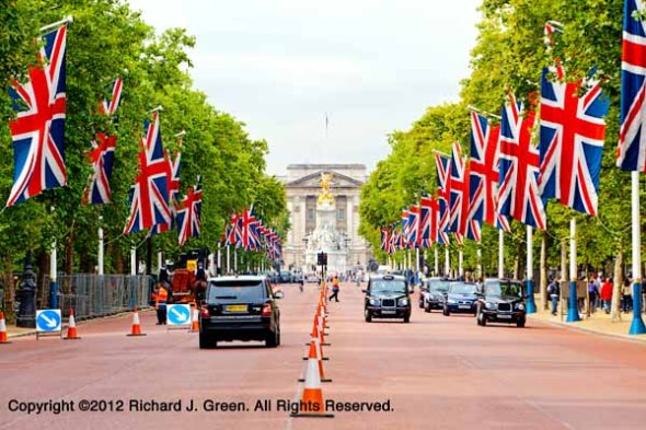 Automobiles driving on The Mall in front of Buckingham Palace.